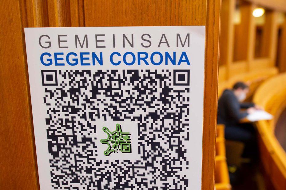 Ein Student sitzt im Hörsaal, im Vordergrund ist ein QR-Code zur Kontaktnachverfolgung sichtbar.